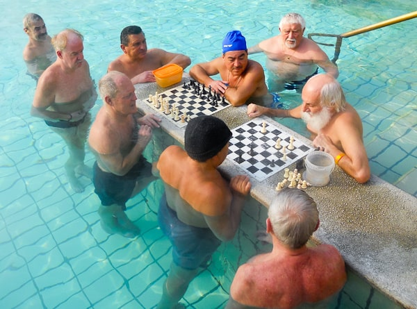 Old men play chess in the water at Szchenyi Baths