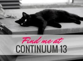 A black cat lazes on concrete