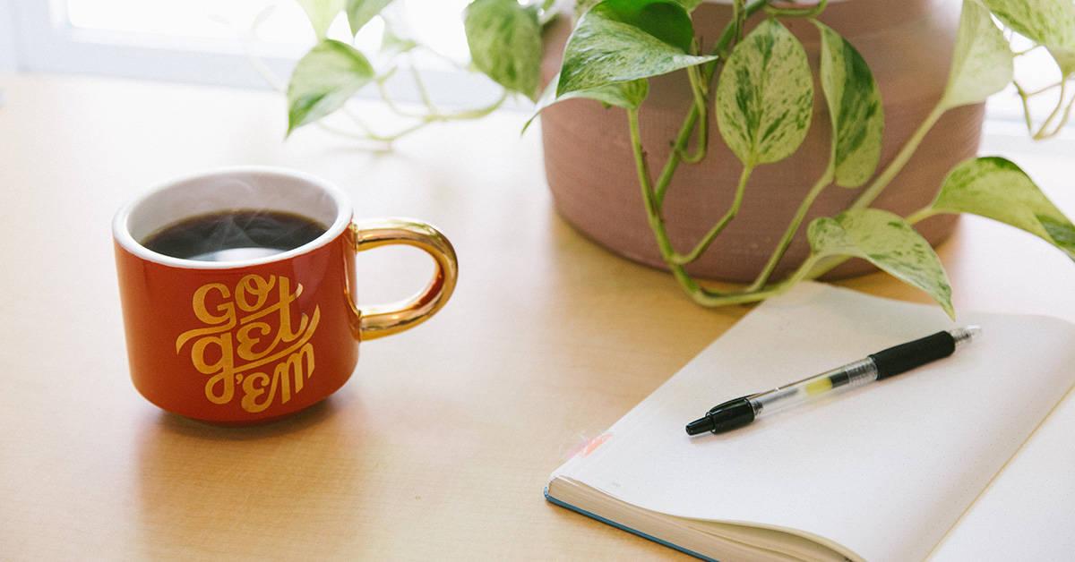 Mug of coffee with words go get em next to a writing notebook