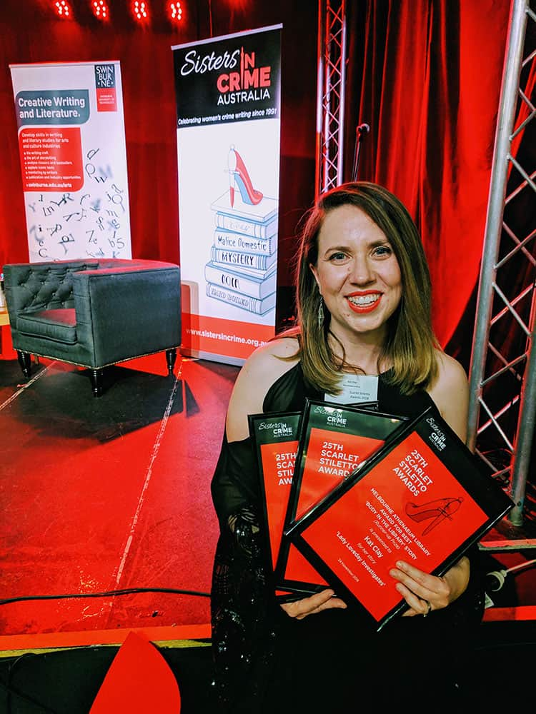 Kat Clay with her three prize certificates for the Scarlet Stiletto Awards