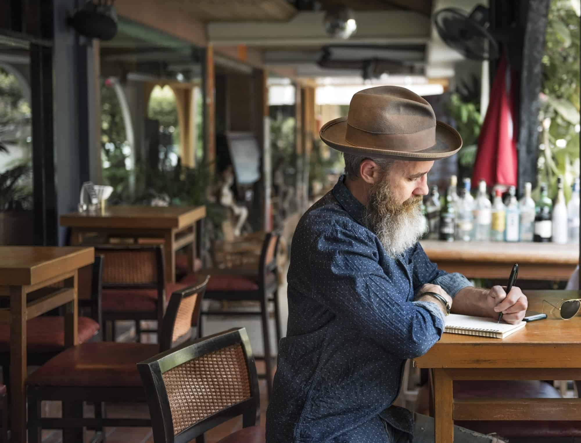 Writer with beard in cafe working