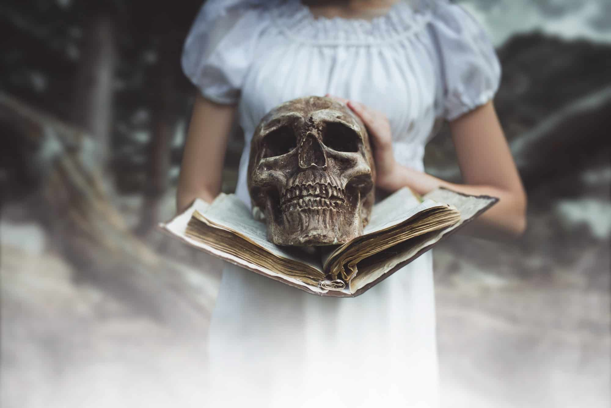 Woman holds book and human skull in hand